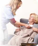 caregiver giving blanket to patient