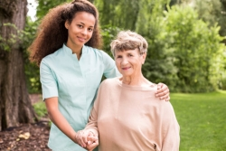 young caregiver in uniform and her senior patient
